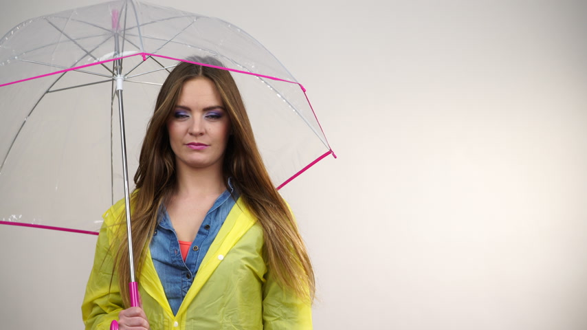 hanedan arması : Woman rainy girl in waterproof yellow coat standing with transparent umbrella stretching arm, holds out her palm to catch rain falling water. Forecasting weather season concept 4K ProRes HQ codec