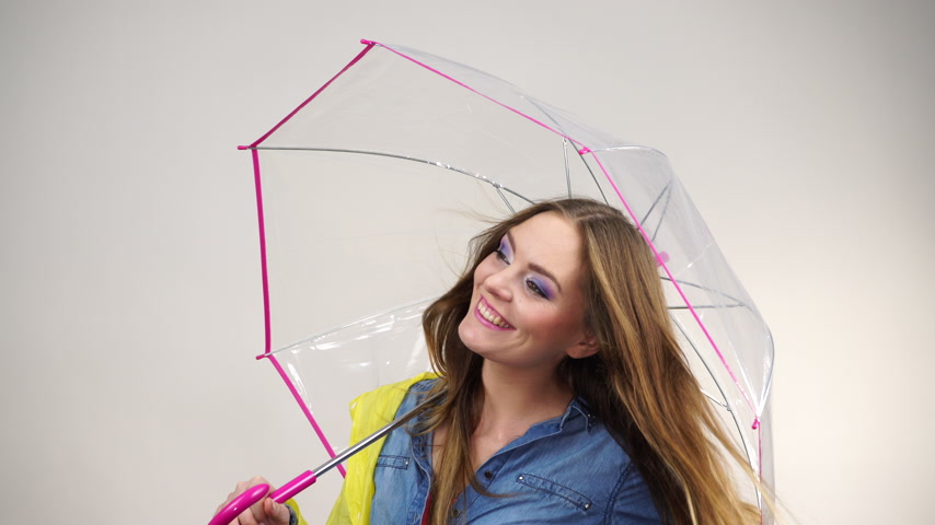 impermeabile : Woman fashionable rainy girl wearing rainproof yellow coat holding transparent umbrella studio shot. Meteorology, forecasting and weather season concept 4K ProRes HQ codec