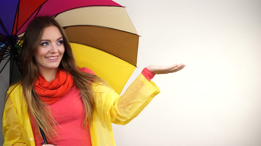 impermeabile : Woman fashionable rainy girl wearing rainproof yellow coat standing under colorful umbrella stretching arm, holds out her palm to catch rain falling water studio shot 4K ProRes HQ codec