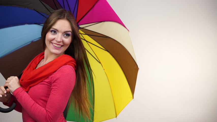 hava durumu : Woman fashionable rainy smiling girl in red clothing standing under colorful umbrella having fun. Meteorology, forecasting and weather season concept 4K ProRes HQ codec Stok Video