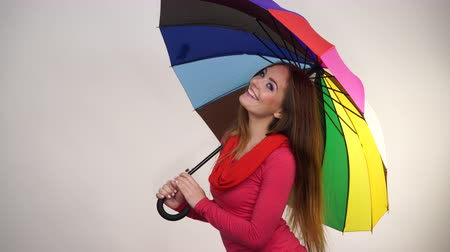 předpovídání : Woman fashionable rainy smiling girl in red clothing standing under colorful umbrella having fun. Meteorology, forecasting and weather season concept 4K ProRes HQ codec Dostupné videozáznamy