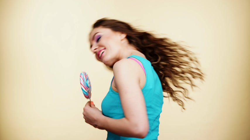 леденец : Woman beautiful cheerful girl holding colorful lollipop candy in hand. Sweet food and happiness concept. Studio shot on bright background 4K ProRes HQ codec