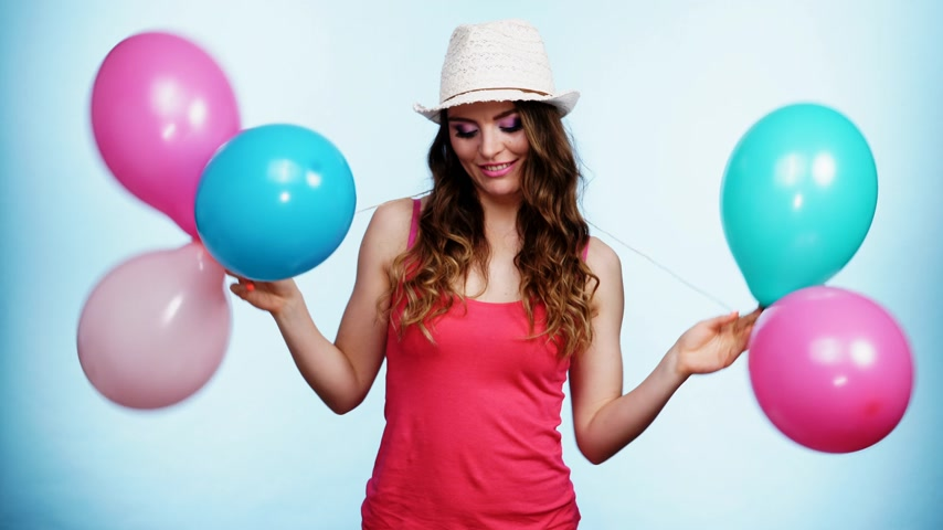 воздушный шар : Woman attractive joyful girl playing with colorful balloons. Summer holidays, celebration and lifestyle concept. Studio shot blue background 4K ProRes HQ codec Стоковые видеозаписи