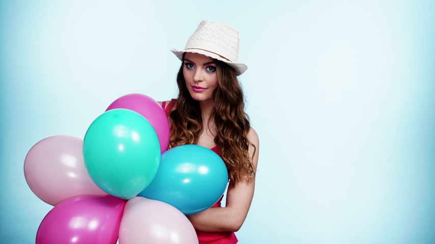 születésnap : Woman attractive joyful girl playing with colorful balloons. Summer holidays, celebration and lifestyle concept. Studio shot blue background 4K ProRes HQ codec Stock mozgókép