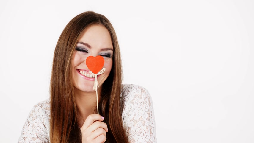 amado : Woman attractive long hair girl holding red wooden heart on stick, charming joyful girl studio shot on white. Valentines day love happiness concept. 4K ProRes HQ codec