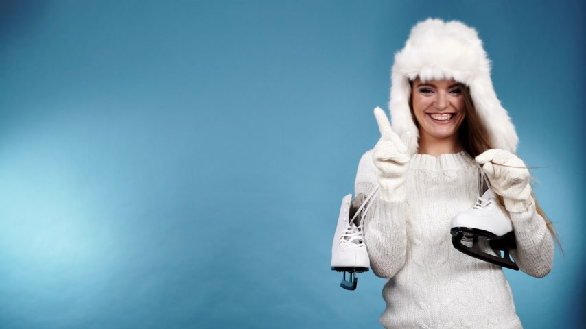 ice skating : Woman with ice skates getting ready for ice skating. Winter sport activity. Smiling girl wearing warm clothing sweater and fur cap on blue studio shot 4K ProRes HQ codec Stock Footage