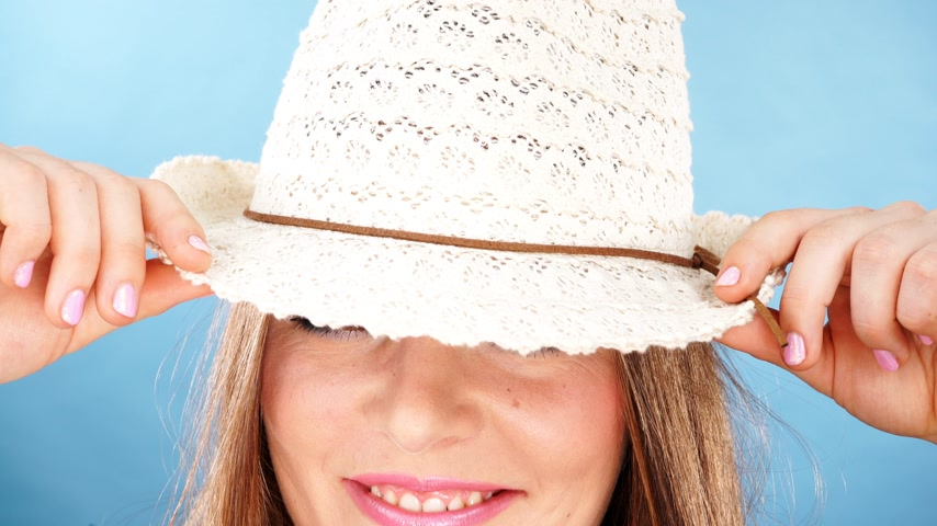 dişlek : Woman face colorful eyes makeup summer straw hat on head smiling having fun closeup. Summer holidays and happiness, studio shot on blue 4K ProRes HQ codec