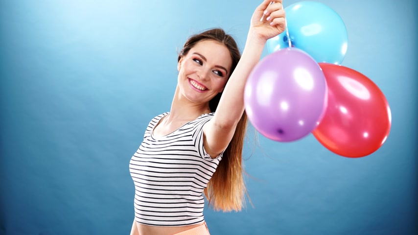 anniversary wishes : Woman attractive joyful girl playing with colorful balloons. Summer holidays, celebration and lifestyle concept. Studio shot blue background 4K ProRes HQ codec Stock Footage