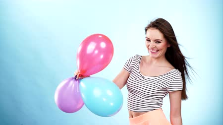 balão : Woman attractive joyful girl playing with colorful balloons. Summer holidays, celebration and lifestyle concept. Studio shot blue background 4K ProRes HQ codec Stock Footage