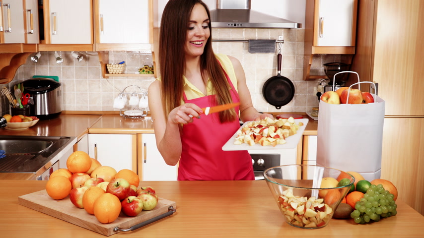 tábua de cortar : Woman young housewife in kitchen at home slicing apple on cutting board and throwing fruits into bowl. Healthy eating, cooking, vegetarian food, dieting and people concept. 4K ProRes HQ codec