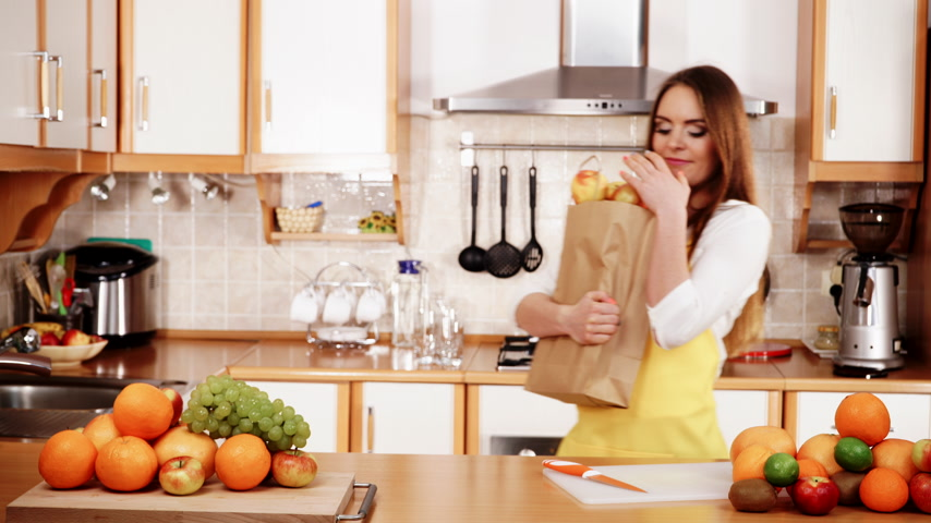 grejpfrut : Woman young housewife in kitchen holding grocery shopping bag, many fruits on counter. Healthy eating, cooking, vegetarian food, dieting and people concept. 4K ProRes HQ codec
