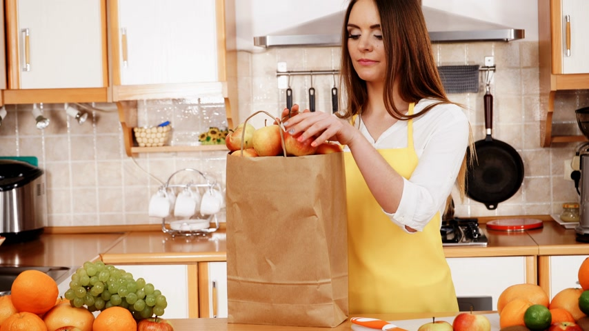 grejpfrut : Woman young housewife in kitchen with grocery shopping bag, many fruits on counter. Healthy eating, cooking, vegetarian food, dieting and people concept. 4K ProRes HQ codec