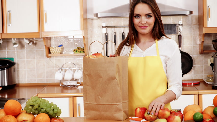 vegetarianismo : Woman young housewife in kitchen with grocery shopping bag, many fruits on counter. Healthy eating, cooking, vegetarian food, dieting and people concept. 4K ProRes HQ codec