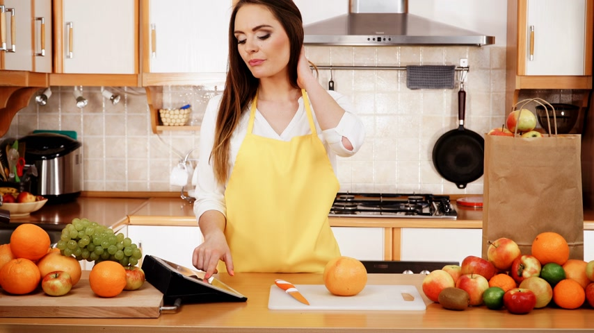 vegetarianismo : Woman young housewife in kitchen with many fruits on counter using tablet looking at recipes. Healthy eating, cooking, vegetarian food, dieting and technology concept. 4K ProRes HQ codec