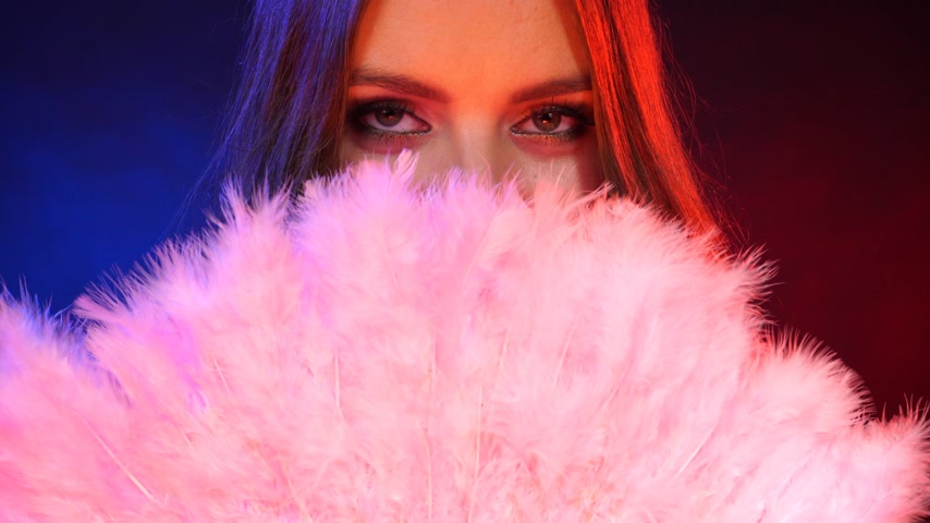 pokrývka hlavy : Woman beauty girl eyes makeup holds carnival pink feather fan in hand, covering her face dark background. Party new year celebration concept. 4K ProRes HQ codec