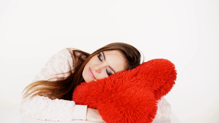 deprivation : Woman hugging tender big red heart love symbol, tired girl sleeping. Health balance sleep deprivation concept. Female student or worker with lack of slumber on white 4K ProRes HQ codec. Stock Footage