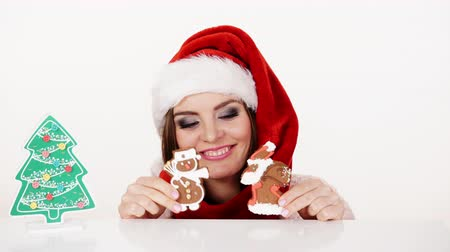 sněhulák : Woman santa claus helper hat playing with gingerbread cookies little snowman and claus. Happy girl awaiting christmas holidays 4K ProRes HQ codec