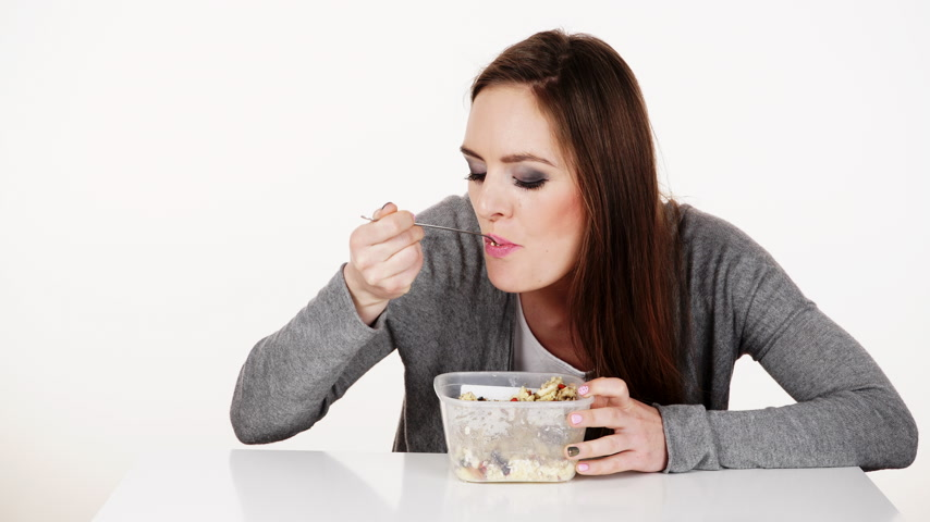 owies : Woman eating oatmeal with nuts and dried fruits for breakfast. Girl holds plastic container take homemade lunch with healthy eating. Dieting nutrition concept. 4K ProRes HQ codec.