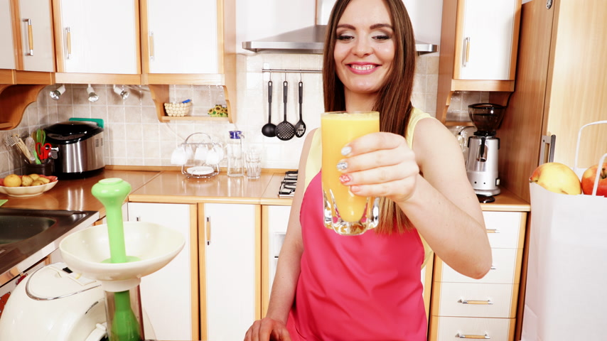 césar : Woman young housewife in kitchen at home drinking fresh homemade orange juice drink making thumb ub gesture. Healthy eating, vegetarian food, weight loss and people concept. 4K ProRes HQ codec