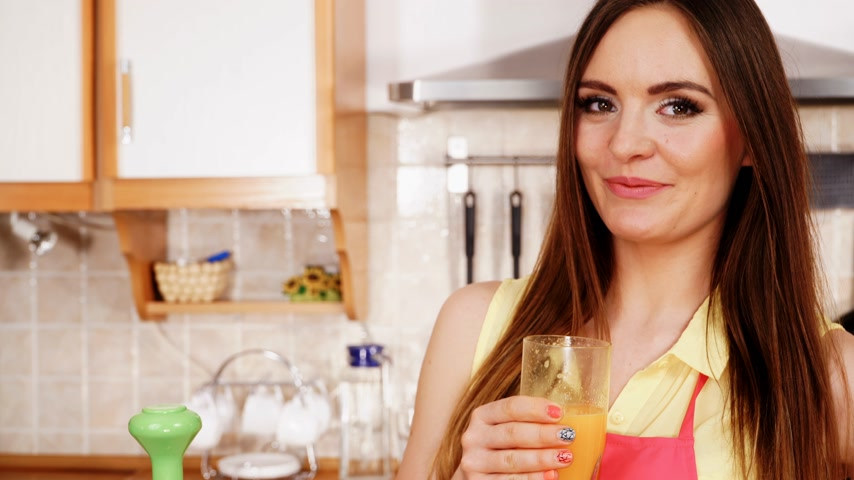 Woman young housewife in kitchen at home drinking fresh homemade orange juice drink. Healthy eating, vegetarian food, weight loss and people concept. 4K ProRes HQ codec