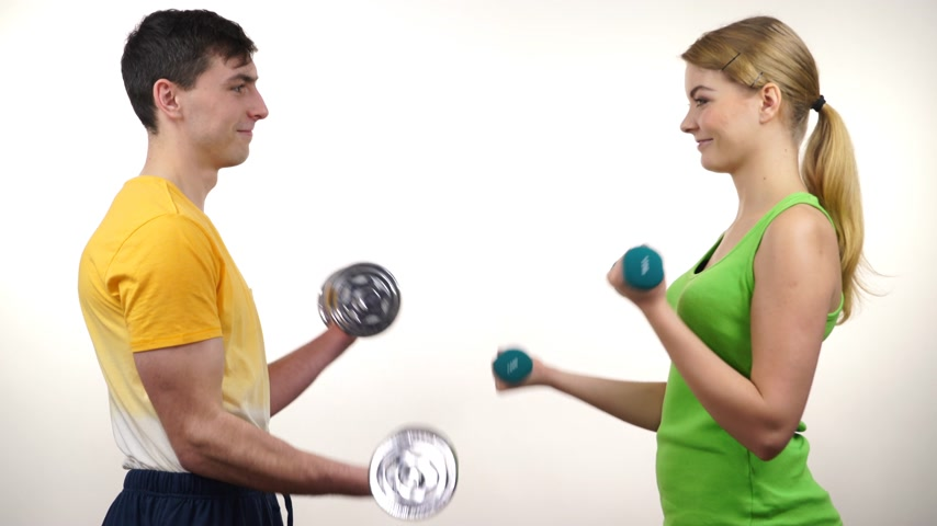 Couple fit woman and strong man exercising with dumbbells. Muscular guy and fitness blonde girl lifting weights Bodybuilding. 4K ProRes HQ codec Stock Footage