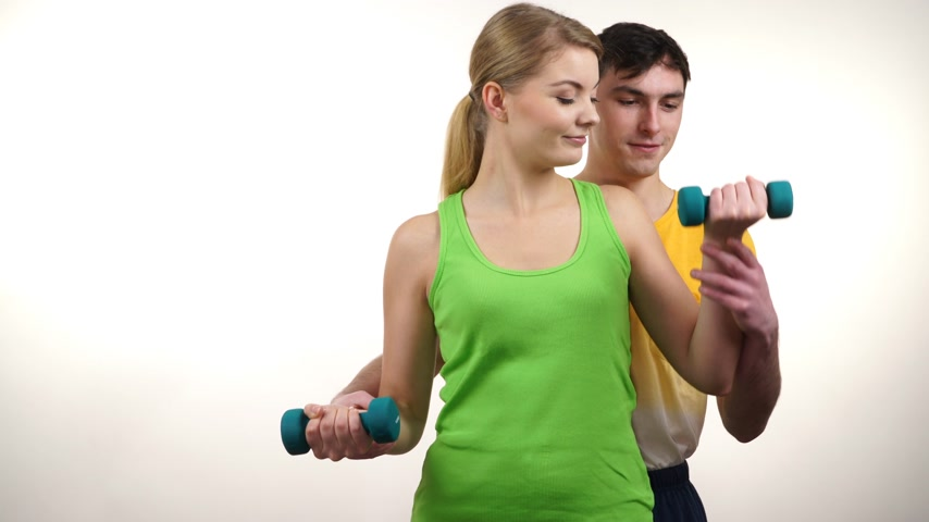 Couple in gym. Woman lifting weights with help from instructor and fitness trainer. Fit girl and strong man exercising with dumbbells. Bodybuilding. 4K ProRes HQ codec