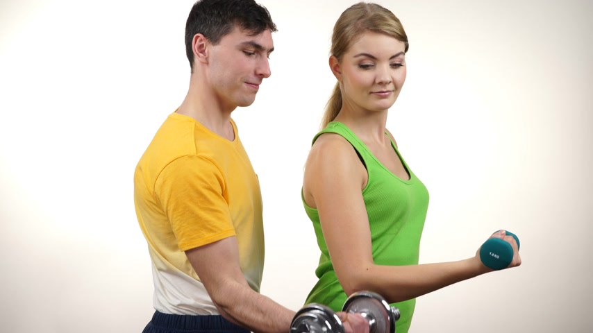 Couple fit woman and strong man exercising with dumbbells. Muscular guy and fitness blonde girl lifting weights Bodybuilding. 4K ProRes HQ codec Wideo