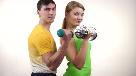 weightlifting : Couple fit woman and strong man exercising with dumbbells. Muscular guy and fitness blonde girl lifting weights Bodybuilding. 4K ProRes HQ codec Stock Footage