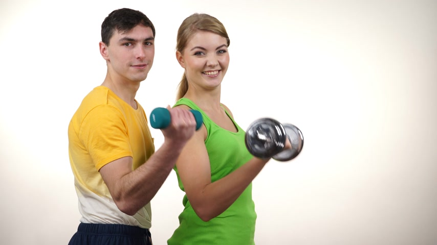Couple fit woman and strong man exercising with dumbbells. Muscular guy and fitness blonde girl lifting weights Bodybuilding. 4K ProRes HQ codec Стоковые видеозаписи
