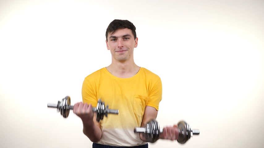 Man exercising with dumbbells. Muscular strong guy lifting heavy weights. Bodybuilding. 4K ProRes HQ codec