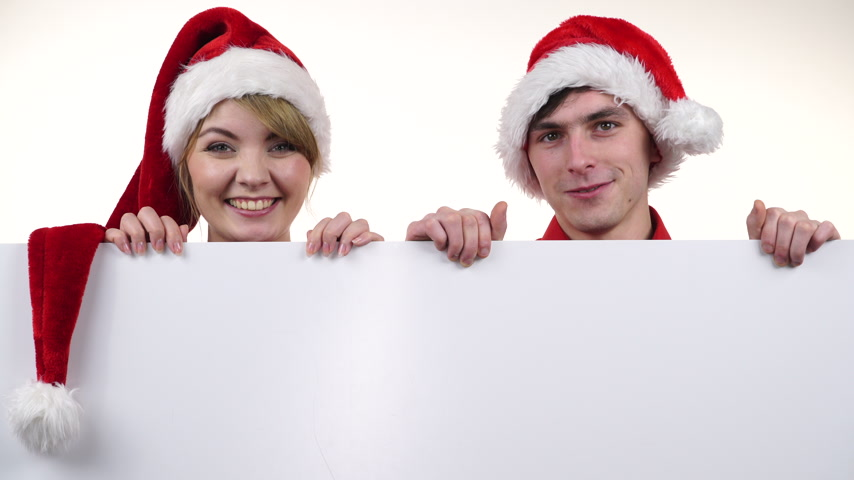 Couple with blank empty banner board. Happy woman and man in santa claus hat. Christmas advertisement copyspace. 4K ProRes HQ codec.