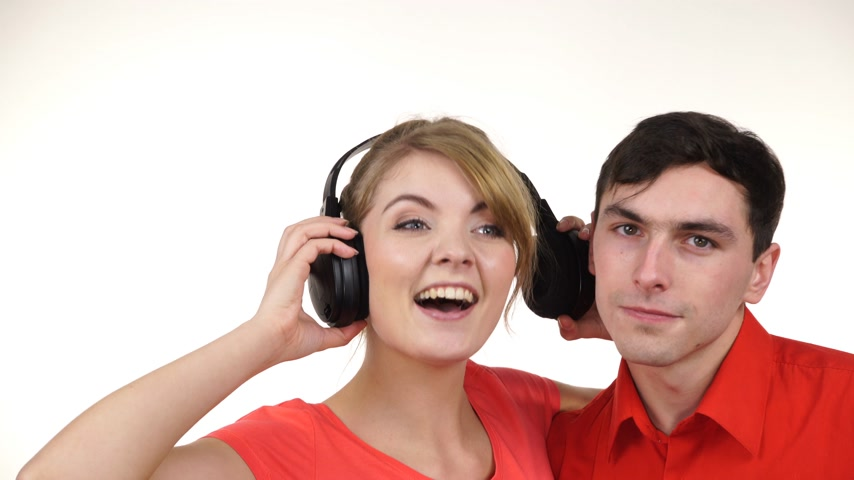 ouvir : Couple two friends with big headphones listening to music mp3 together. Joyful happy woman and man on white. People leisure happiness concept. 4K ProRes HQ codec Stock Footage