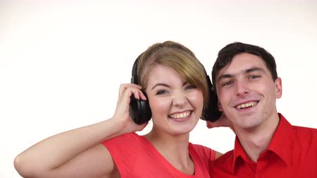 listens : Couple two friends with big headphones listening to music mp3 together. Joyful happy woman and man on white. People leisure happiness concept. 4K ProRes HQ codec Stock Footage