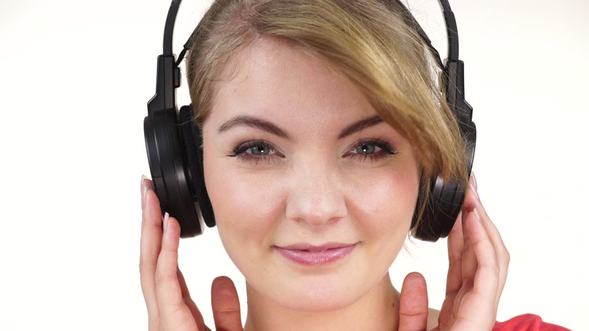 listens : Woman casual style big headphones listening music mp3 closeup. Smiling female model on white. People leisure happiness concept. 4K ProRes HQ codec