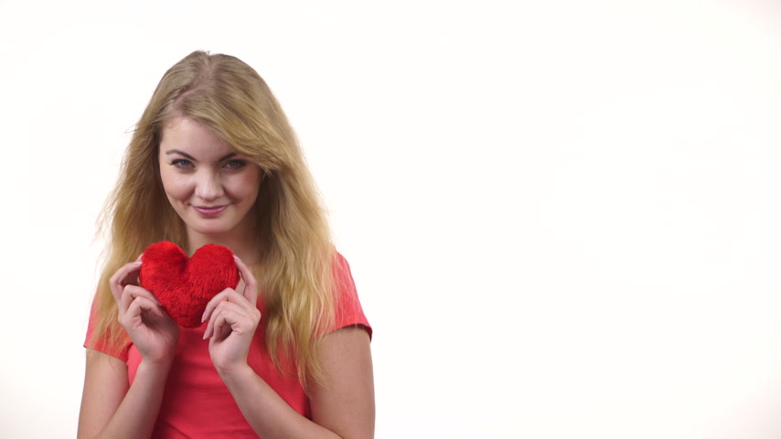 amado : Woman blonde long hair girl holding red heart love symbol studio shot on white. Valentines day happiness concept. 4K ProRes HQ codec