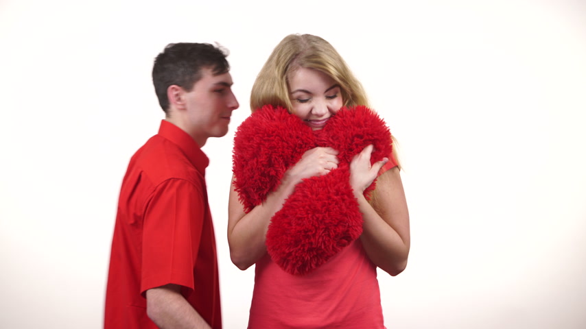 Couple. Boyfriend and his girlfriend holding red heart shaped pillow love symbol. Romantic woman and man hugging. Valentines day happiness concept. 4K ProRes HQ codec
