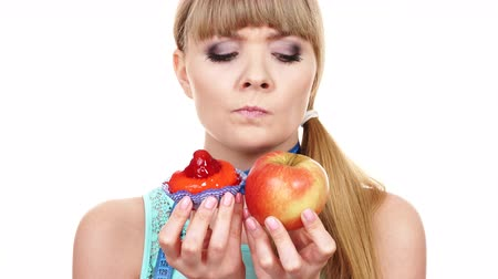 doubt : Woman with measuring tape holds in hand cake and apple fruit choosing, trying to resist temptation, make the right dietary choice. Weight loss diet dilemma gluttony concept. 4K ProRes HQ codec