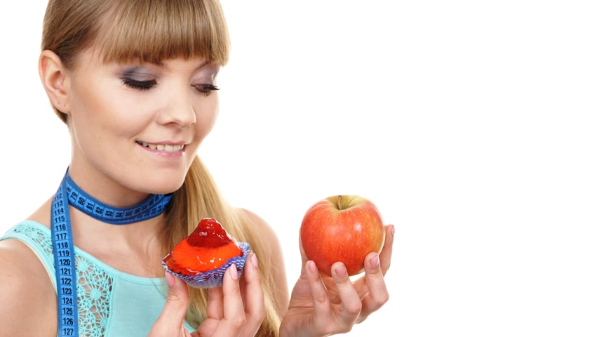 comparar : Woman with measuring tape holds in hand cake and apple fruit choosing, trying to resist temptation, make the right dietary choice. Weight loss diet dilemma gluttony concept. 4K ProRes HQ codec