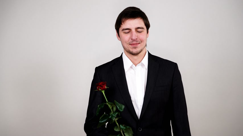повод : Man wearing black suit white shirt holds red rose flower. Anniversary proposal and engagement concept. Studio shot 4K ProRes HQ codec