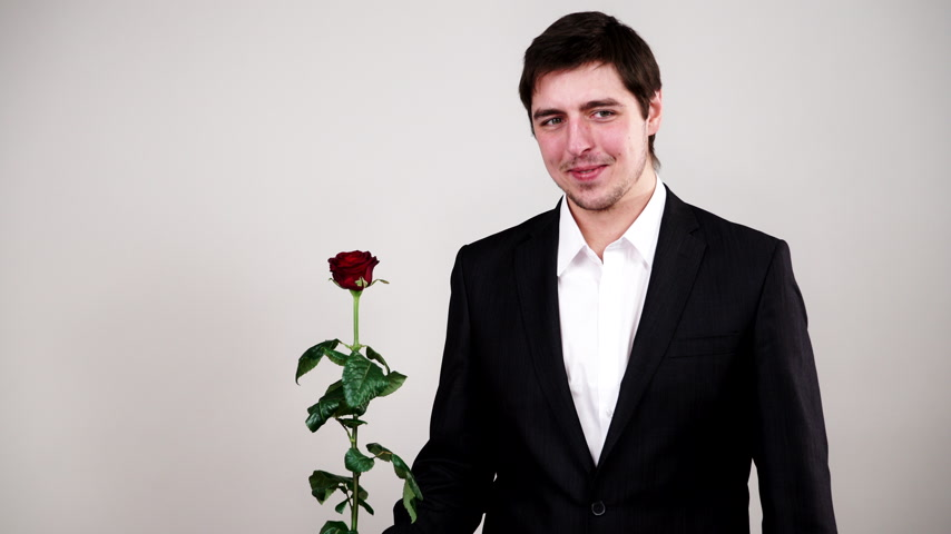 oświadczyny : Man wearing black suit white shirt holds red rose flower. Anniversary proposal and engagement concept. Studio shot 4K ProRes HQ codec