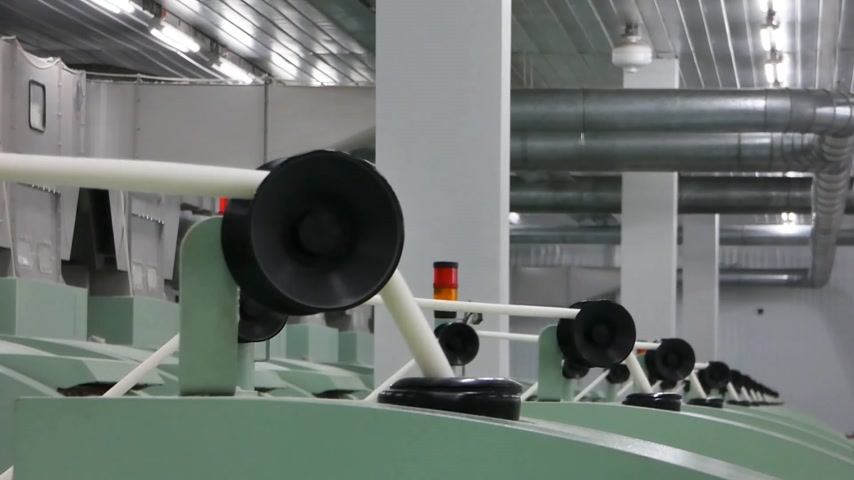 on camera : Machinery and equipment in the workshop for the production of thread. interior of industrial textile factory. the camera is stationary