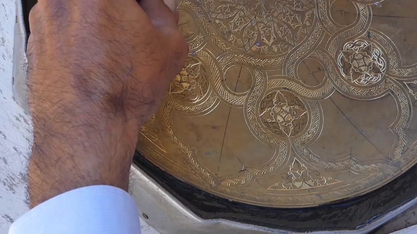 coppersmith : craftsman engraving patterns on the tray. masters of Central Asia and Uzbekistan. manual copper minting. the old art of etching on utensils