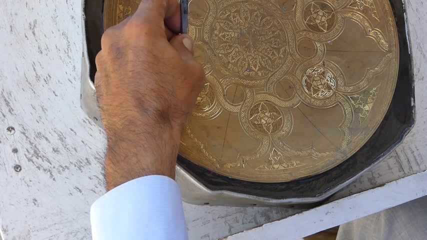 candida : craftsman engraving patterns on the tray. masters of Central Asia and Uzbekistan. manual copper minting. the old art of etching on utensils