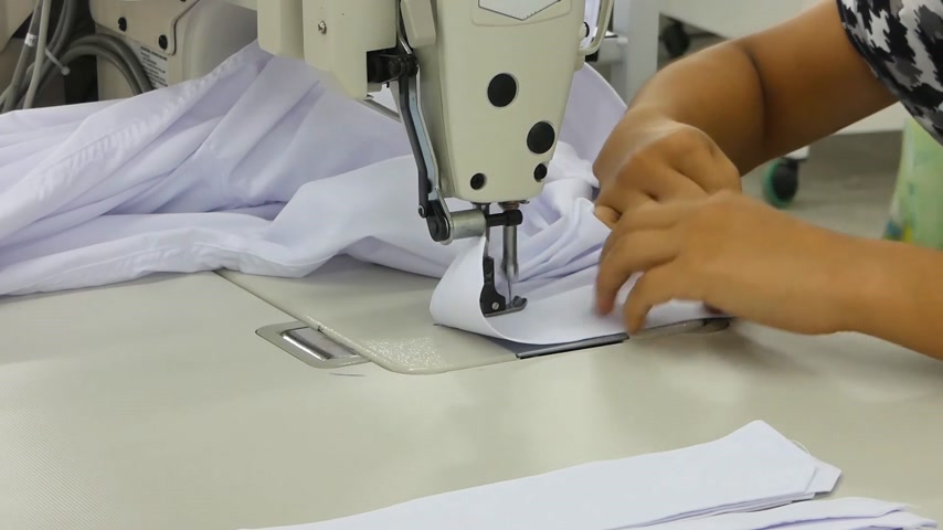 candida : seamstress on a sewing machine. the woman on the machine sews the collar and cuffs