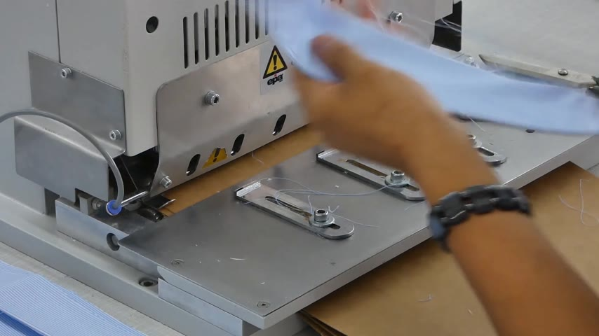 candida : a woman in the sewing shop on the press machine gives the shape of a shirt collar and cuffs