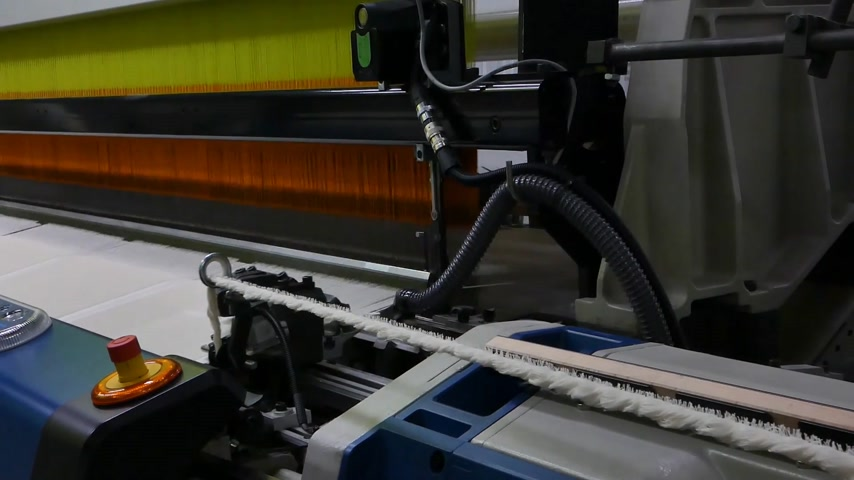 kursor : weaving loom at a textile factory, close-up. industrial fabric production line. the camera is stationary