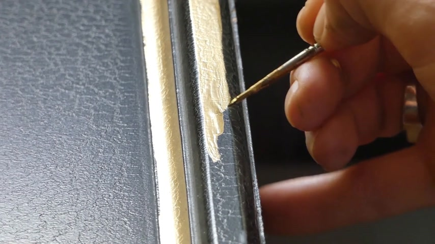 candida : painter decorator draws pattern with a thin brush, close-up