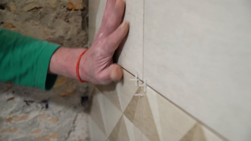 piastrellista : Worker inserts plastic crosses in the seam between tiles. Finishing works, focus on hands. The technology of laying tile.