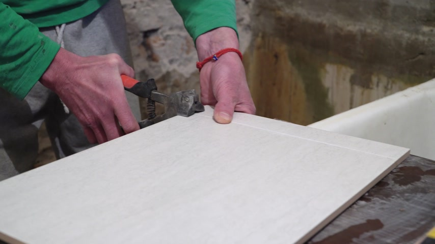 candida : Worker with a hand cutter tile. Finishing works, focus on hands. The technology of laying tile.
