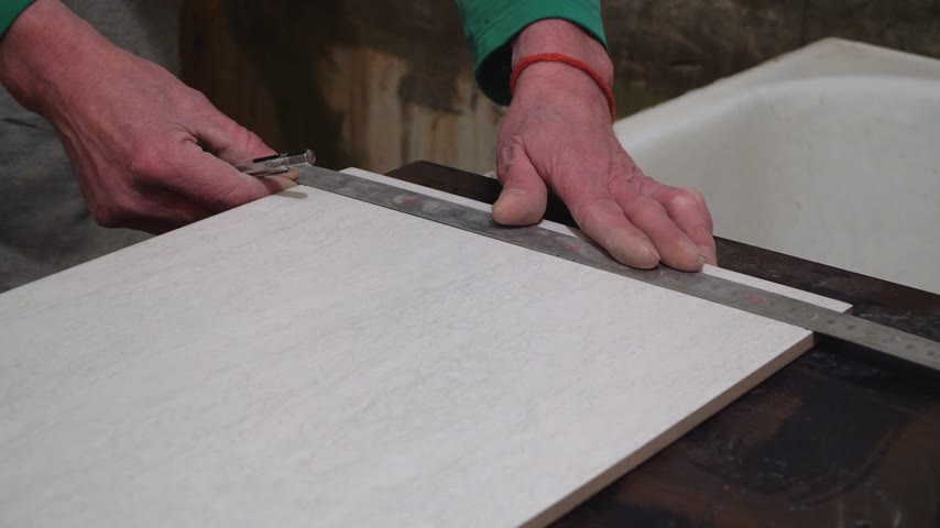 stavitel : Worker with a hand cutter tile. Finishing works, focus on hands. The technology of laying tile.